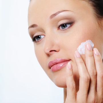 Young beautiful woman caring of her face with moisturizer cream