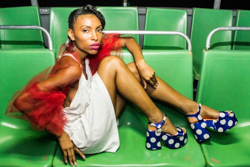 Foto de modelo sentada em uma arquibancada com um par de sandálias de plataforma estampadas com poá
